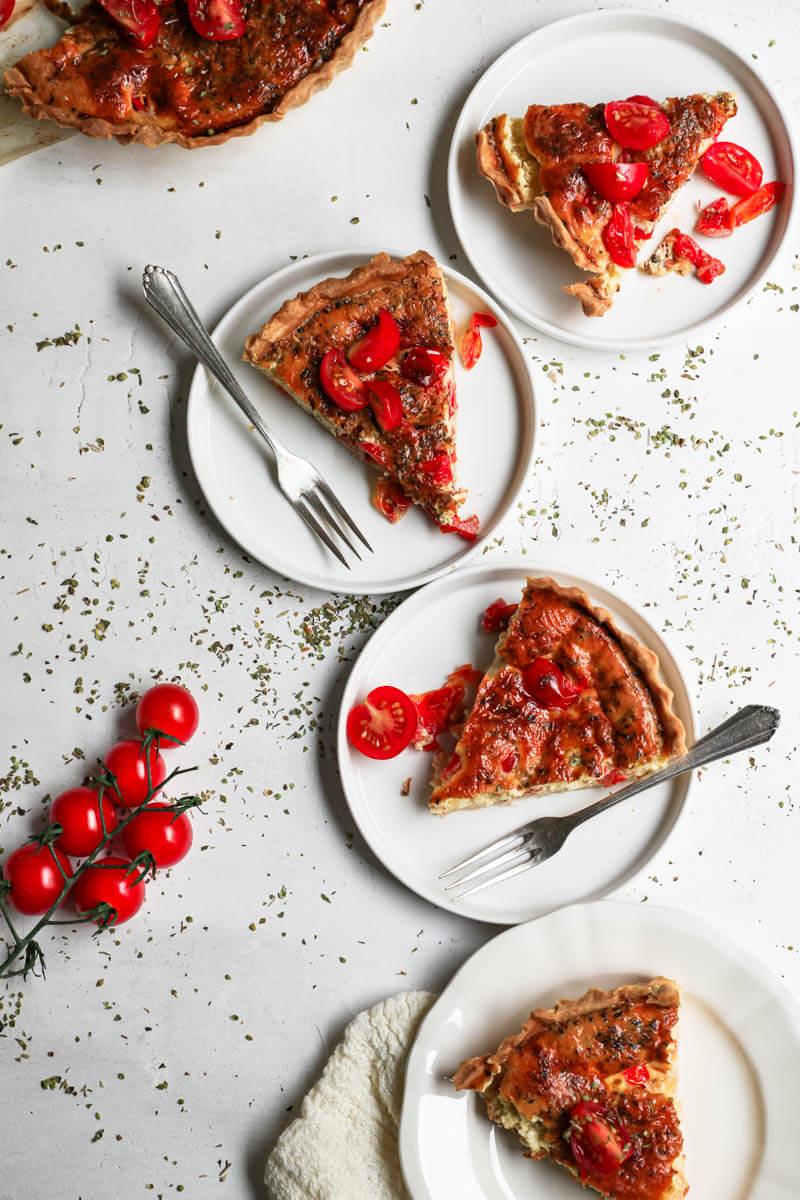 Plano aéreo de 4 platos cada uno con una porción de tarta de tomate y mozzarella