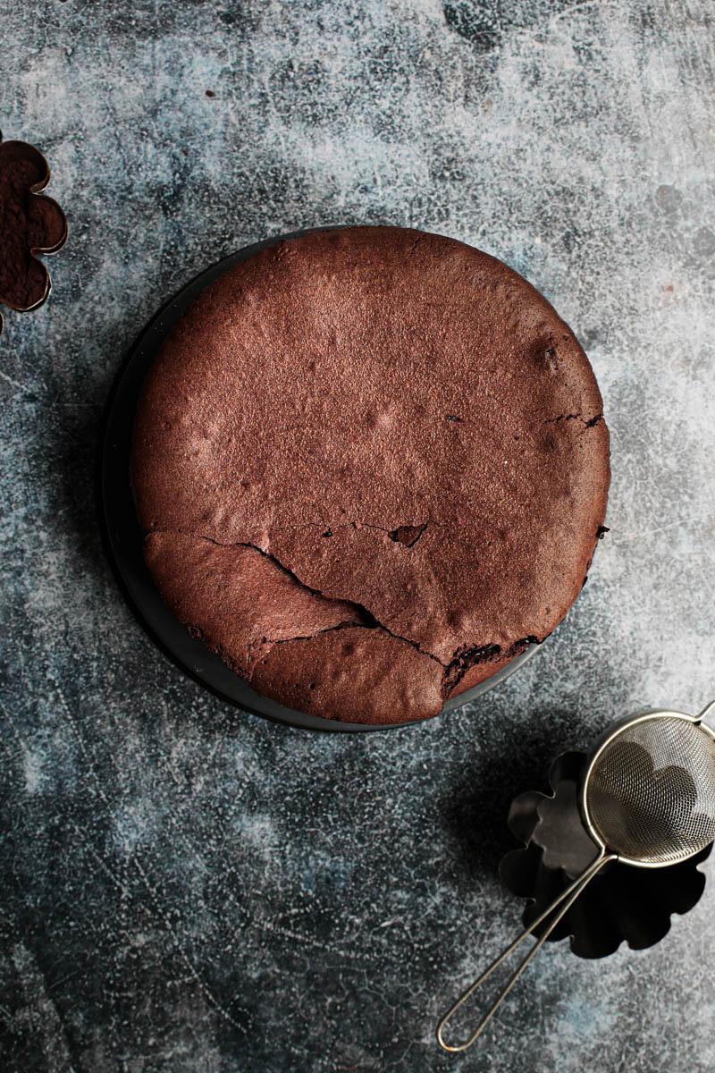 Torta entera de chocolate húmeda recién salida del horno con bol de cacao en polvo a su lado.