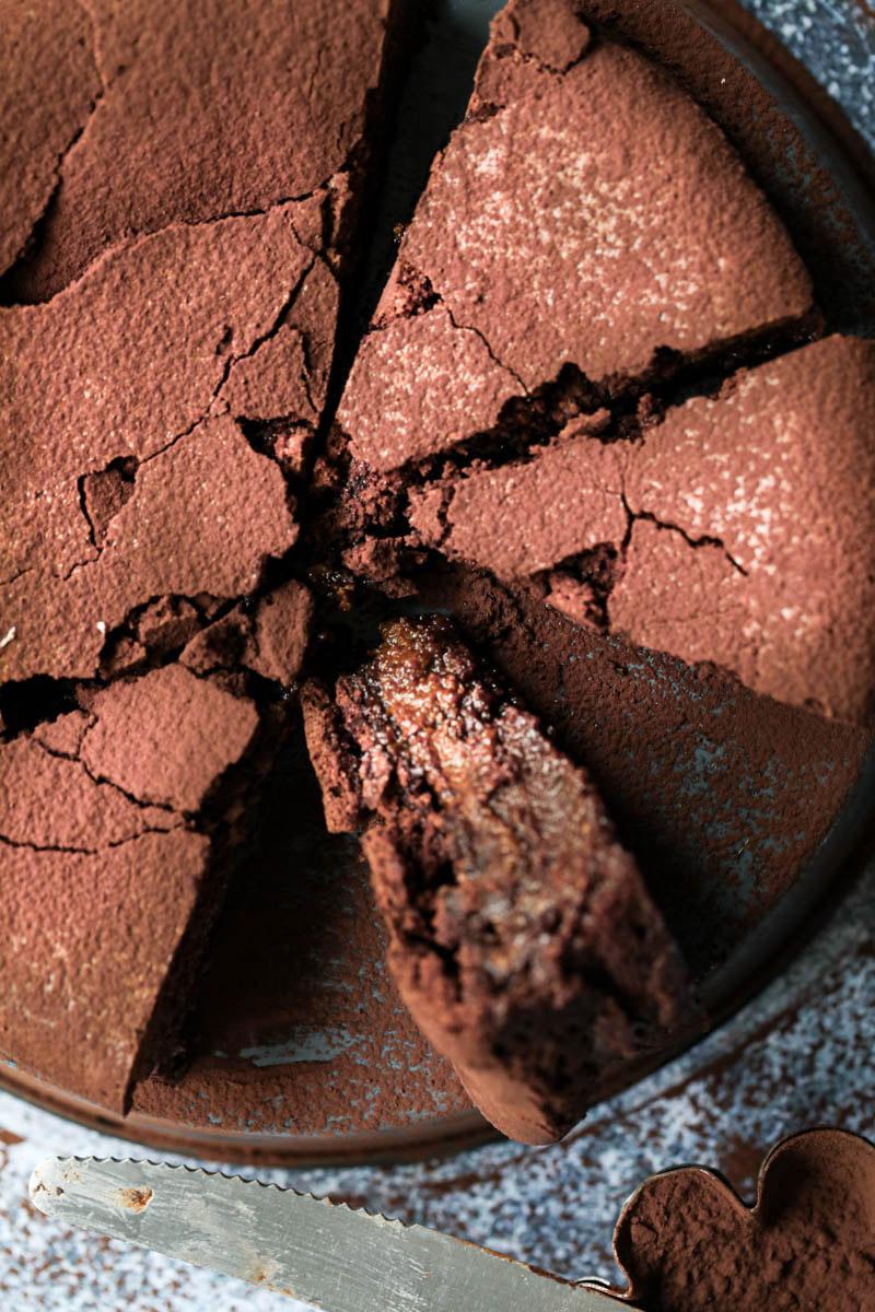Primer plano de un pedazo de torta húmeda de chocolate con un cuchillo a su lado.