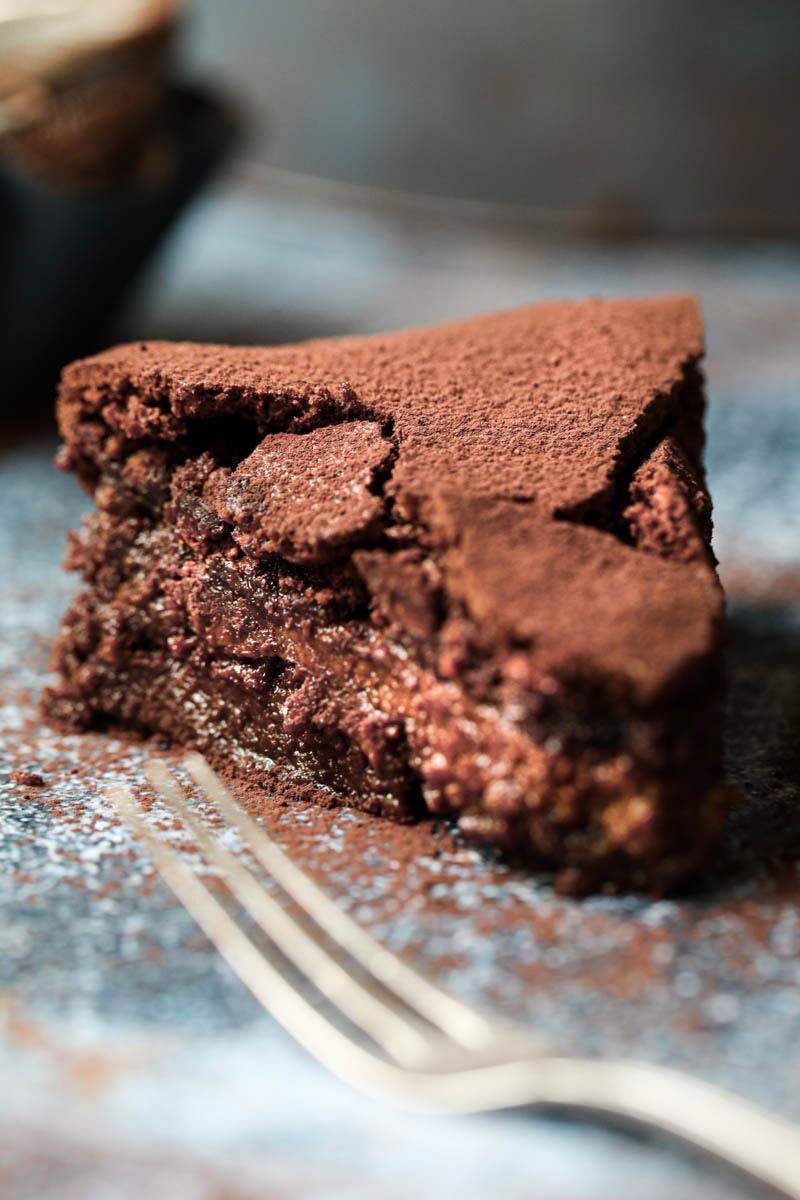 Una porción de torta húmeda de chocolate vista desde el costado derecho con un tenedor delante.