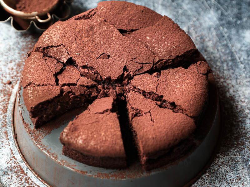 La torta húmeda de chocolate cortada sobre una bandeja gris invertida con un cuchillo al costado y bol con cacao detrás.