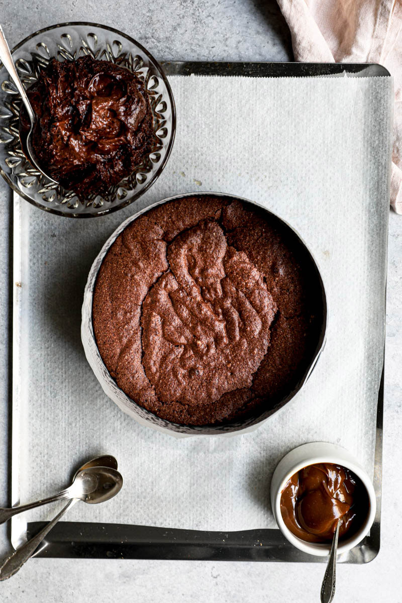 2/3 de la torta de chocolate horneada sobre una placa para horno con un bol con el resto de la mezcla cruda arriba y otro bol con dulce de leche debajo.