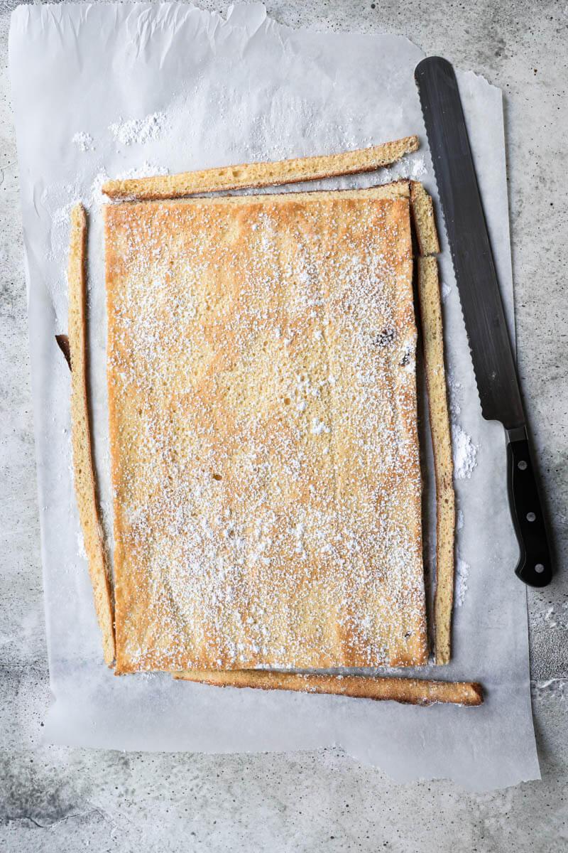 El pionono cocido dado vuelta sobre papel manteca con los bordes cortados