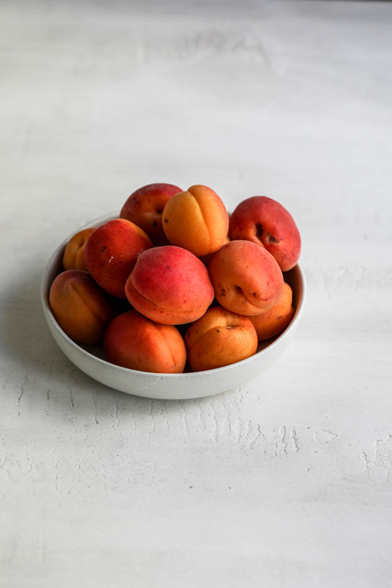 45° shot of a bowl filled with apricots.
