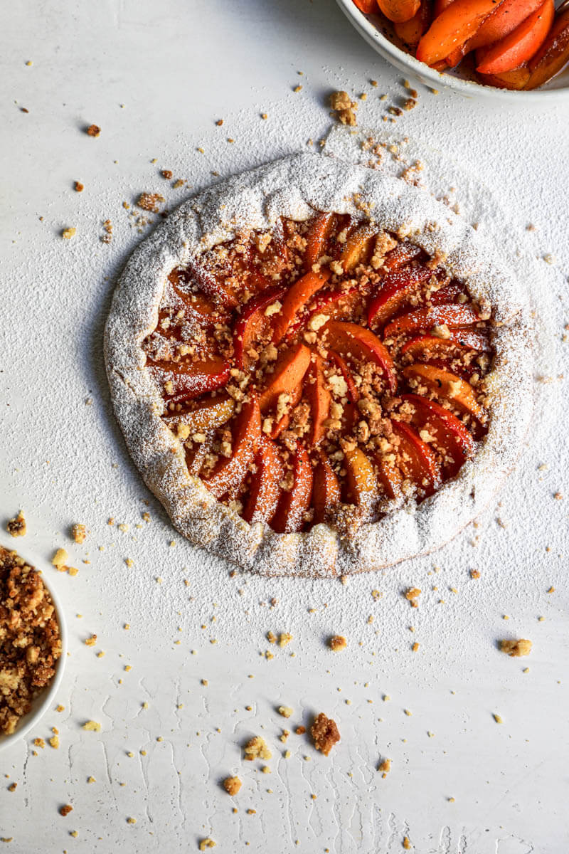 Overhead shot of the baked apricot tart topped with hazelnut crumble and sprinkled with powdered sugar.