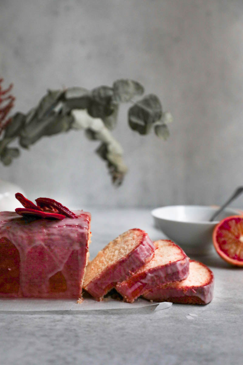 Sliced blood orange cake seen from the side with some leaves in the back and jar on the side.