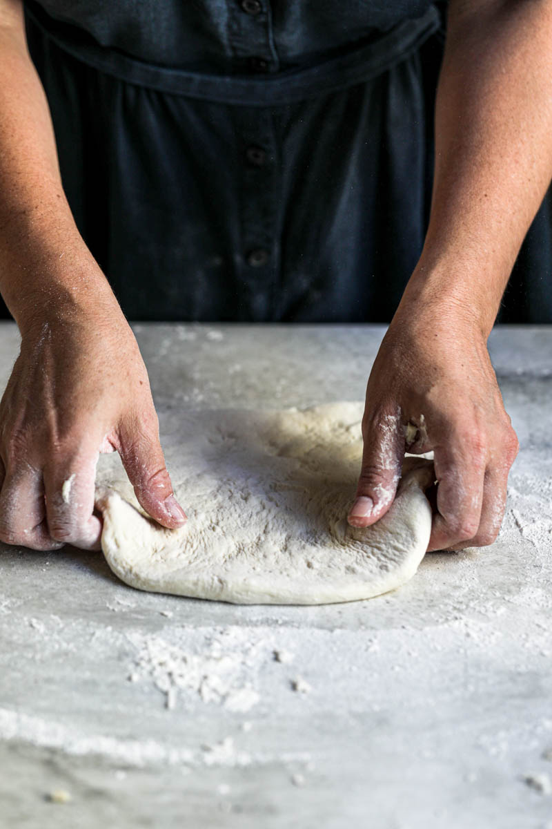 2 hands relaxing the pizza dough before stretching