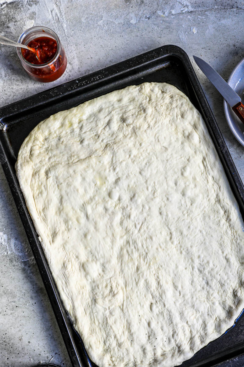 Overhead shot of the pizza dough on the baking tray