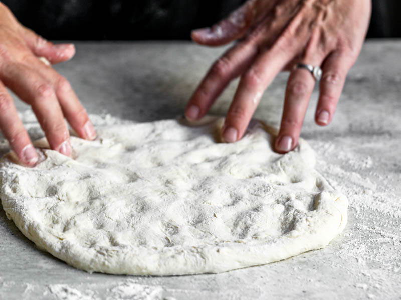45° shot of 2 hands stretching the pizza dough