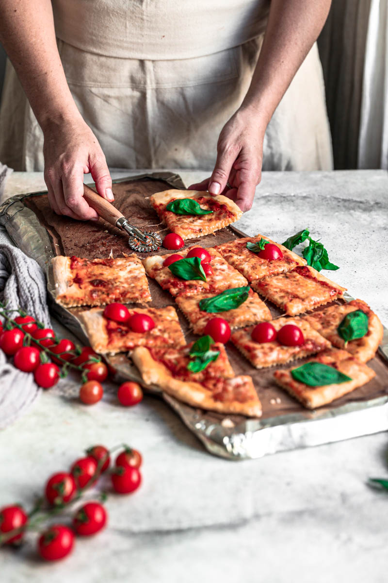 45° shot of 2 hands holding a slice of the baked margherita pizza on a wooden board