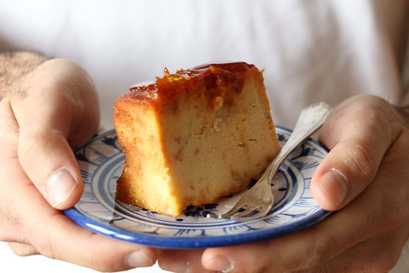 90° shot of two hands holding a plate with one piece of bread pudding