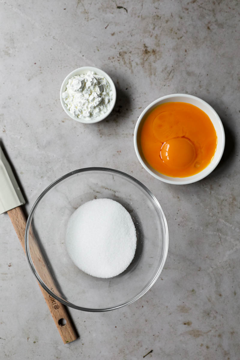 Bowl of sugar, bowl of egg yolks and bowl of corn-starch to make pastry cream.