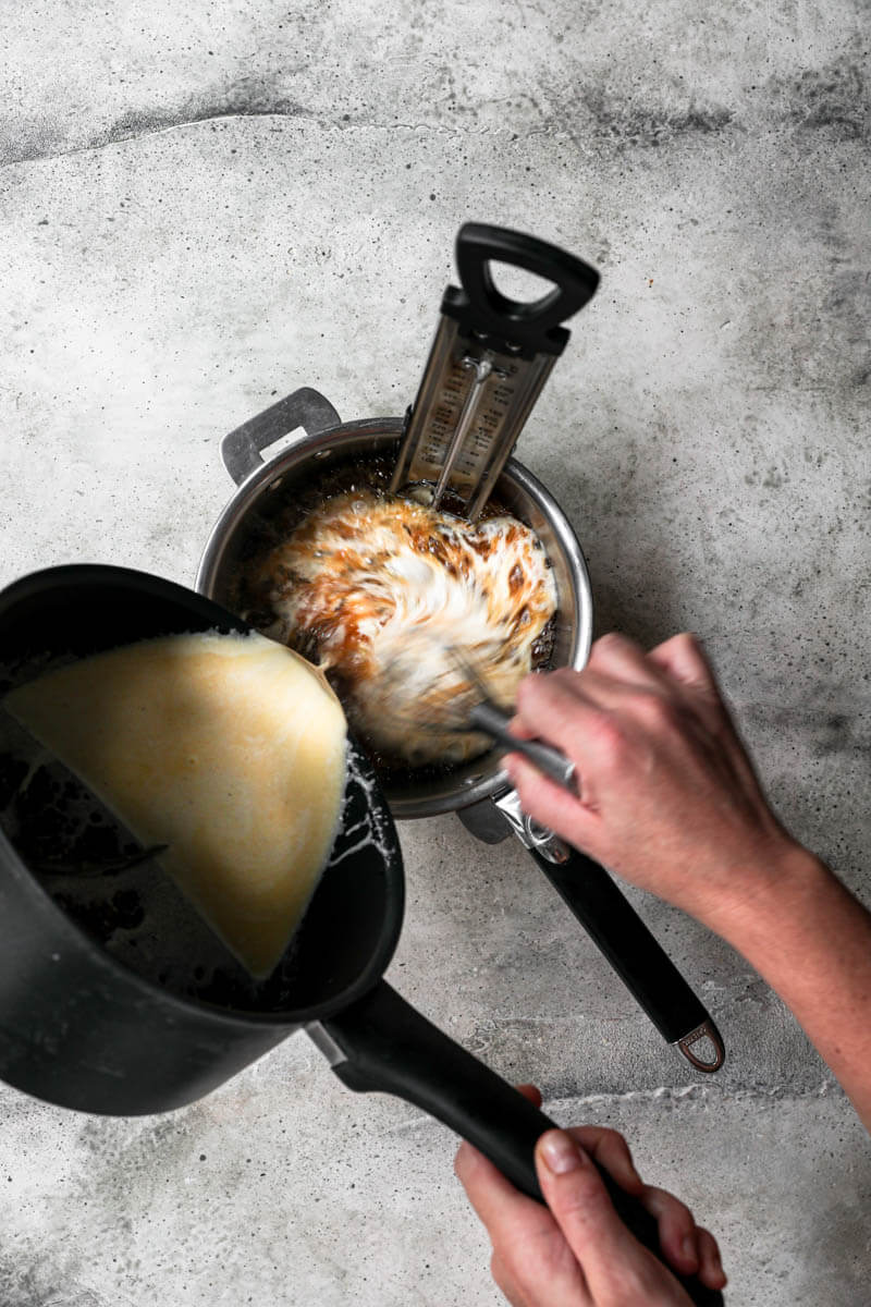 One hand pouring cream and butter over a pan with caramel