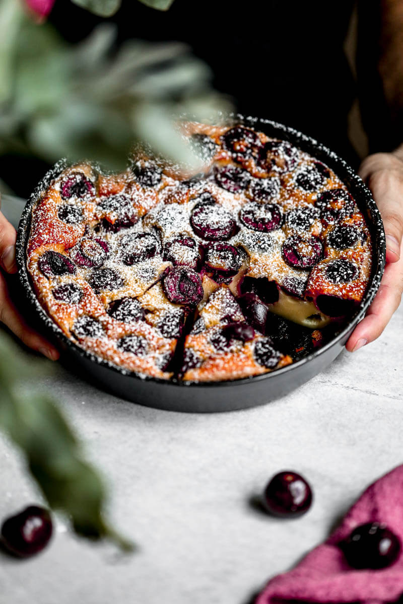 45° shot of 2 hands holding the cherry clafoutis