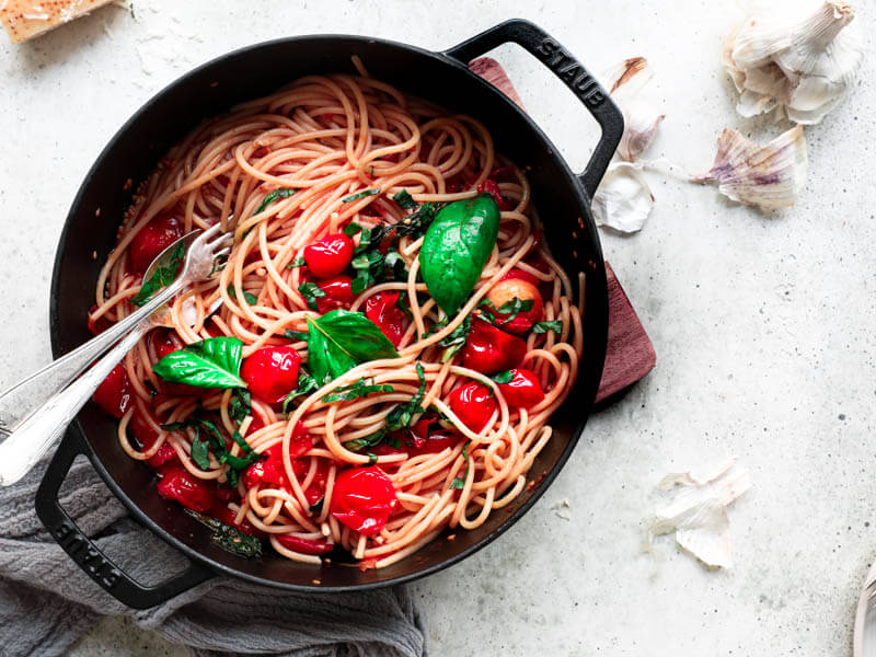 Overhead shot of a black pan filled with pasta and topped with cherry tomato sauce with a fork and a spoon in the corner