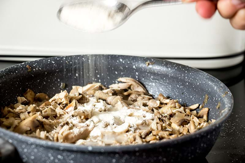 Sprinkling flour onto the chicken and mushroom filling inside the pan