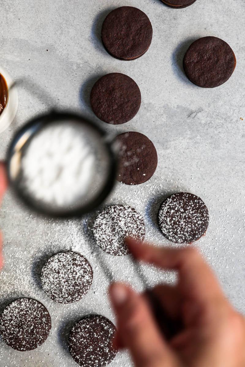 Overhead shot of a hand sprinkling powdered sugar onto the chocolate alfajores