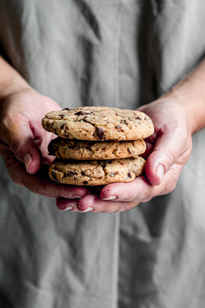 90° shot of 2 hands holding 3 cookies
