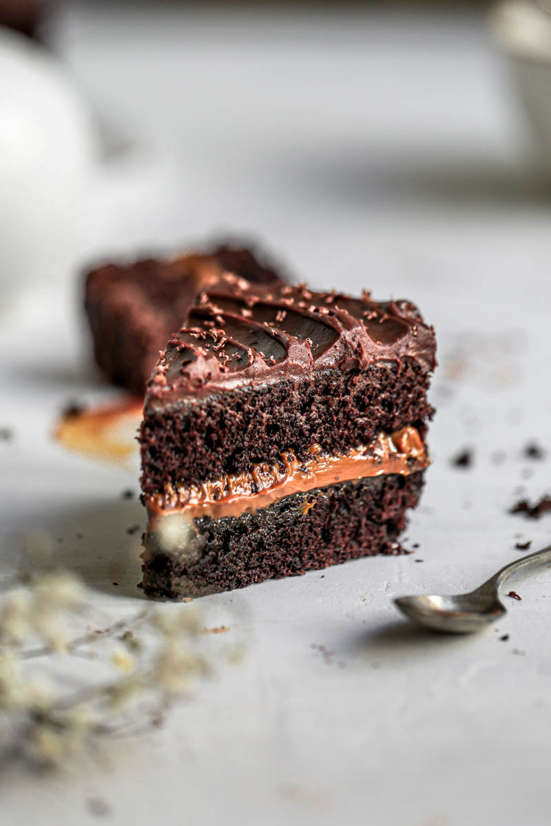 45° shot of one slice of chocolate dulce de leche cake with a spoon out of focus on the right hand side