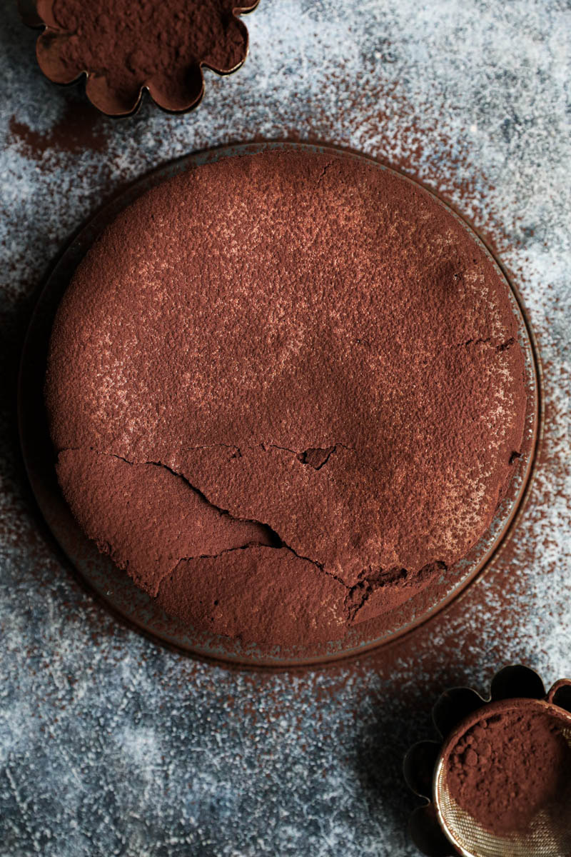 Whole chocolate fudge cake seen from above sprinkled with cocoa powder.