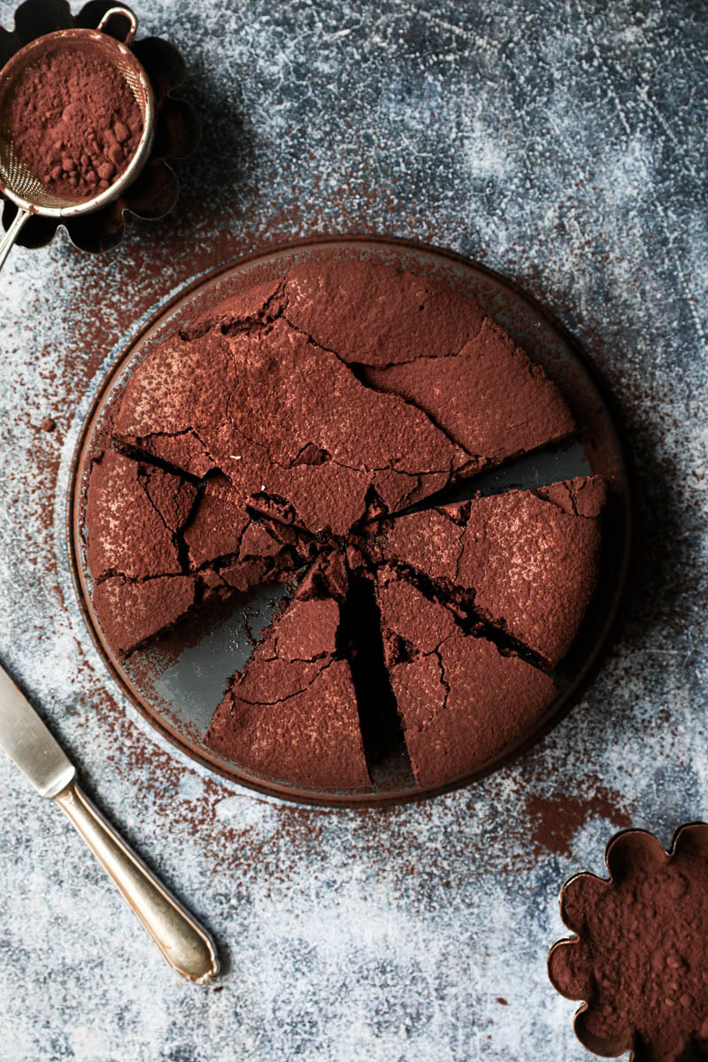 Sliced chocolate fudge on a grey tray with a knife on the side and a bowl with cacao powder on the other side seen from above.