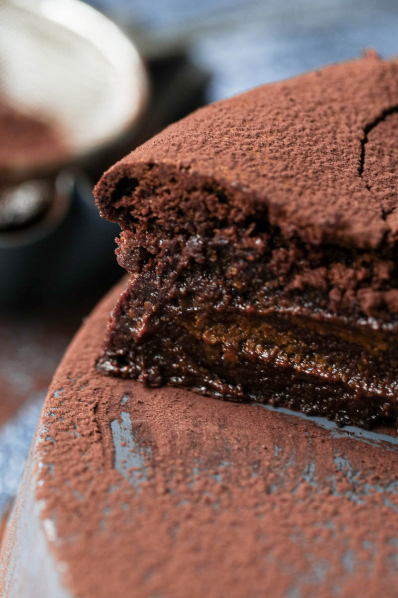 Closeup of a slice of chocolate fudge on a grey tray with cocoa powder around.
