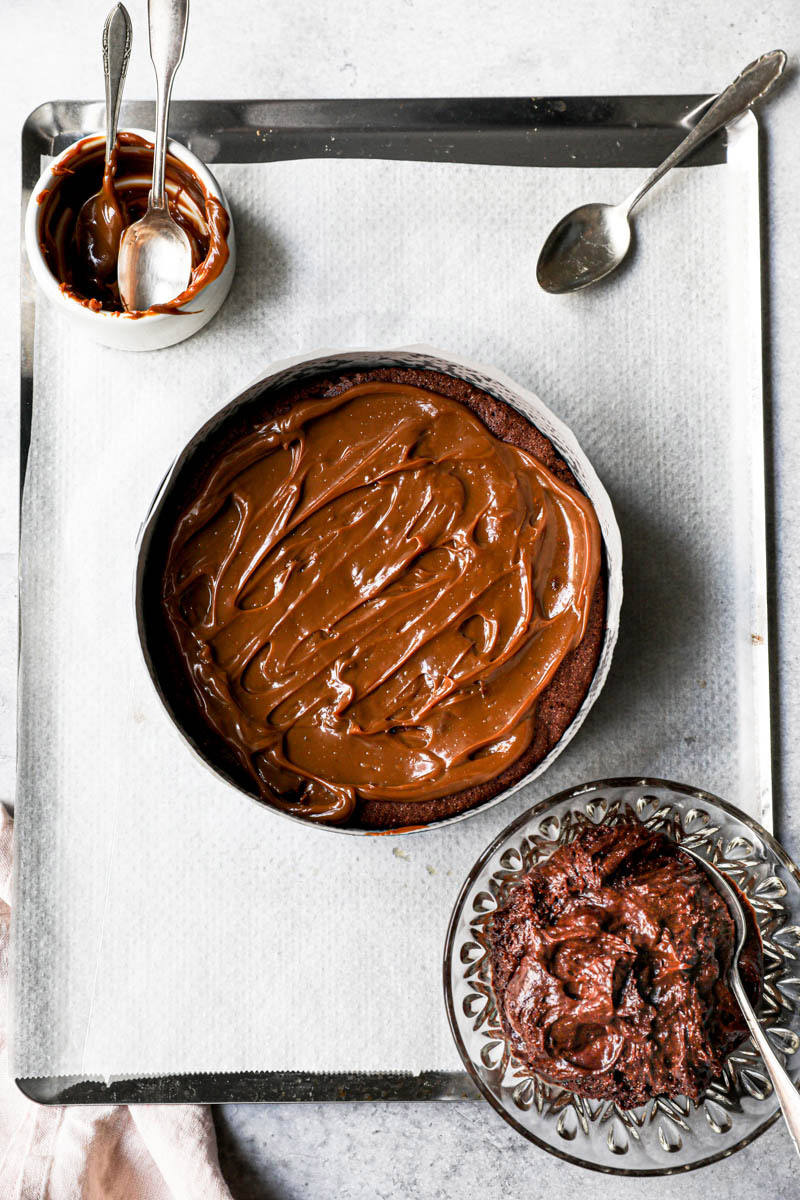 The chocolate fudge cake covered with a thin layer of dulce de leche on top of a baking tray.