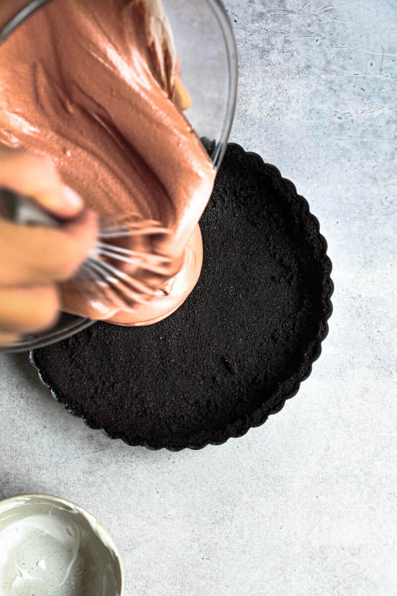 2 hand pouring the chocolate mousse over the oreo pie crust