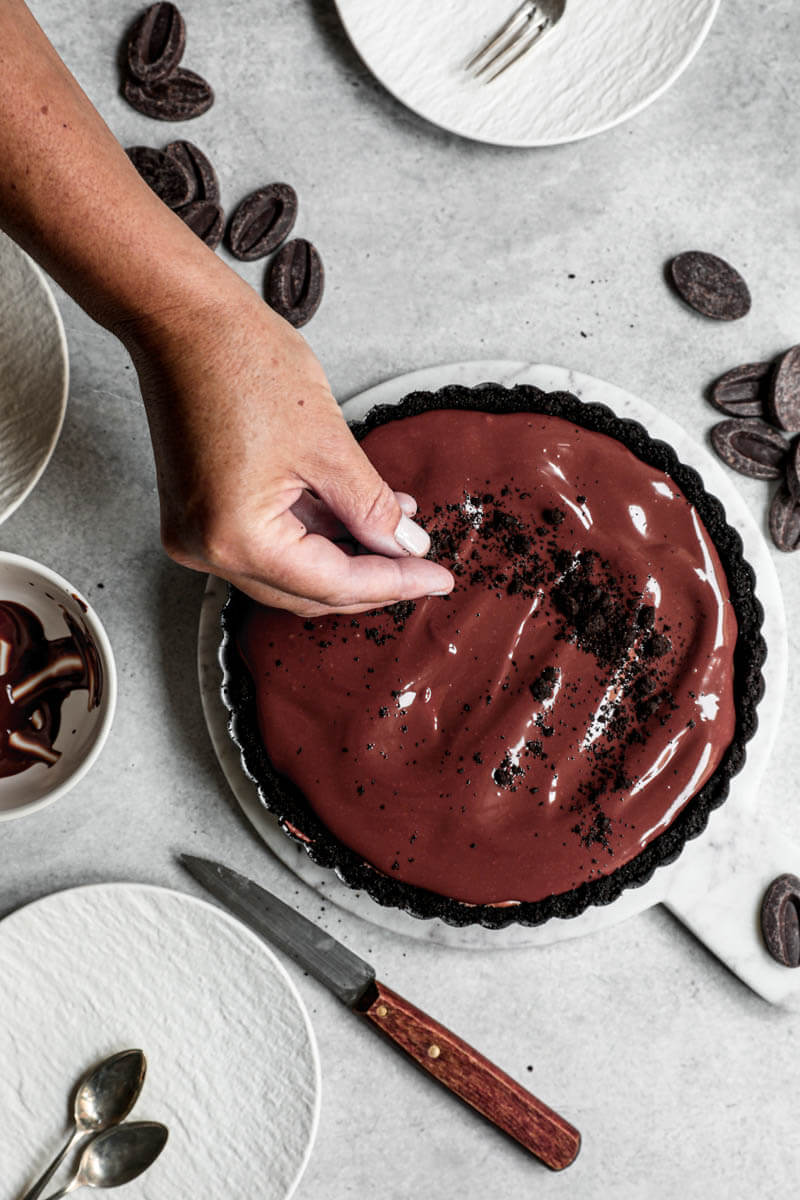 Overhead shot of one hand sprinkling crushed oreos over the chocolate mousse pie