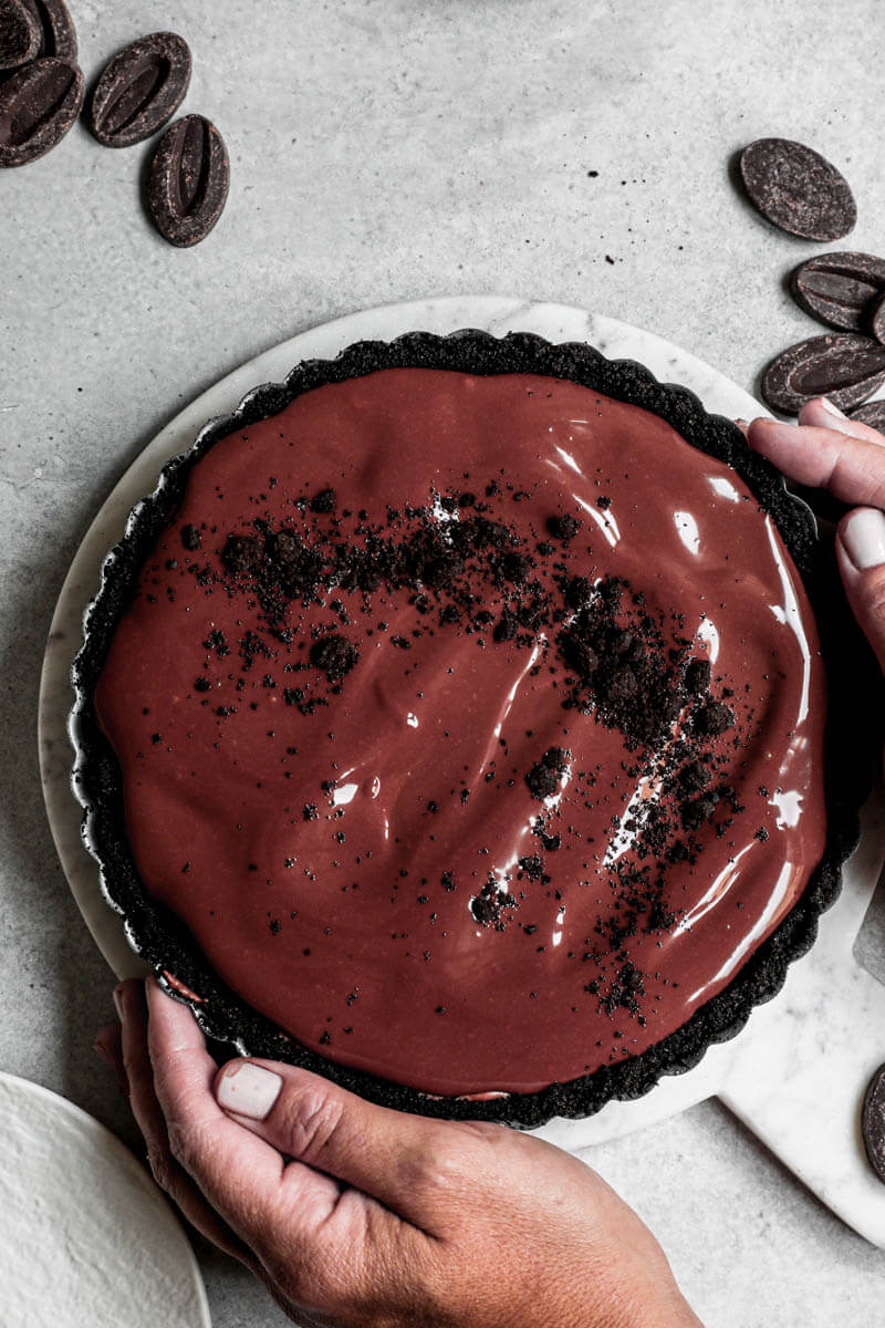 Overhead closeup shot of 2 hands holding the chocolate mousse pie in the pie tin