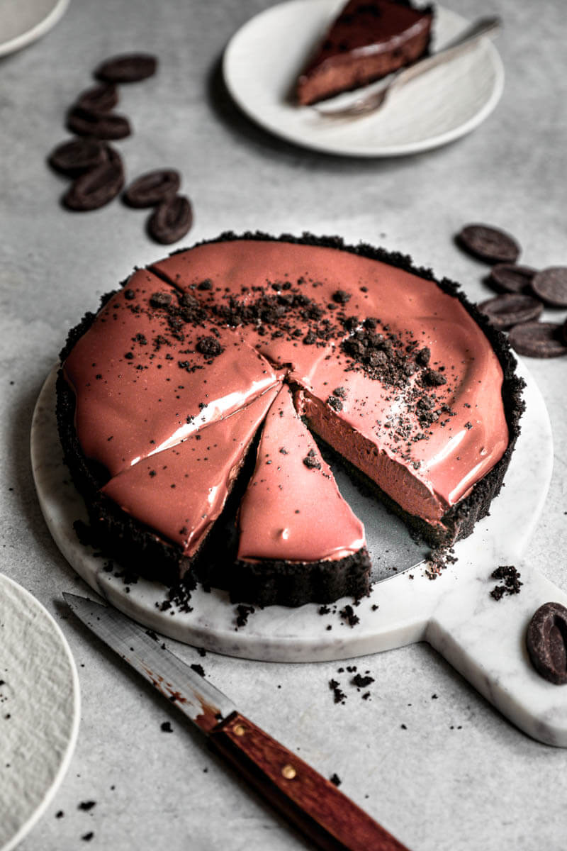 45° shot of the sliced chocolate mousse cake on a marble serving platter with a slice on a plate at the back