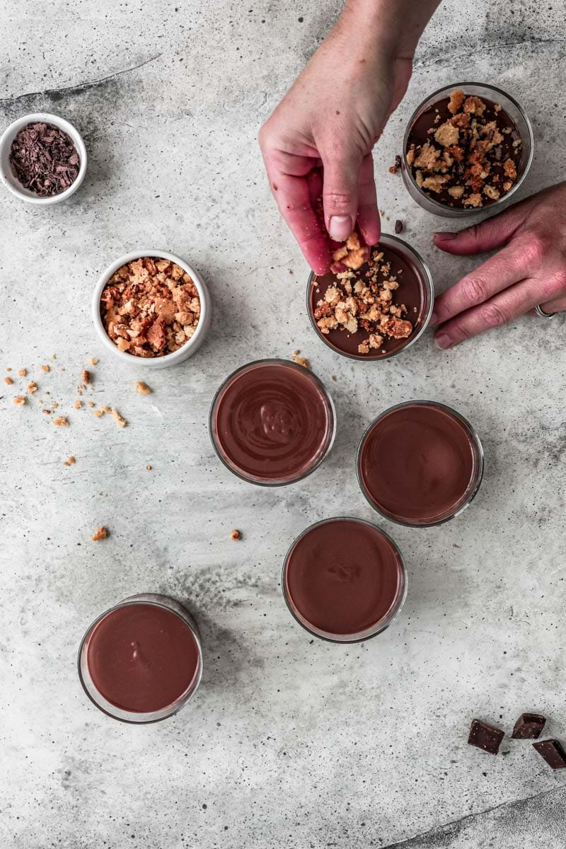 Top the chocolate pots de crème with some crumble topping and chocolate shavings