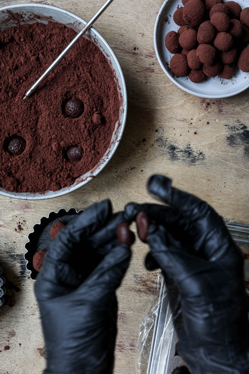 2 hands putting together ganache half balls to form a truffle