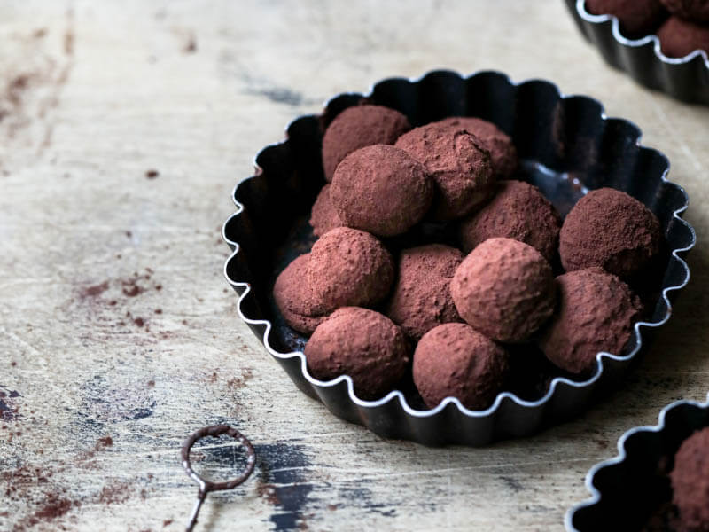 Dark chocolate truffles on a black tart tin