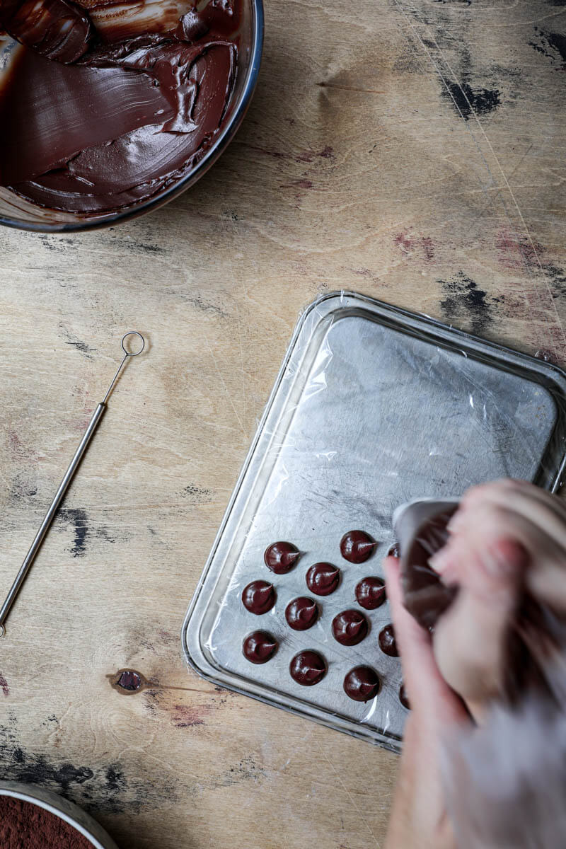 Hand piping chocolate ganache balls on a baking tray