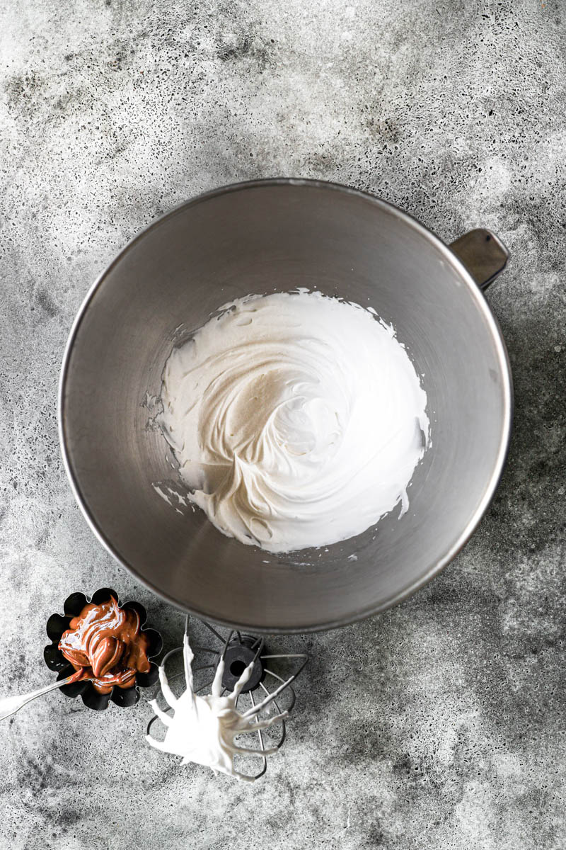 Whipped cream in a mixing bowl and dulce de leche on the side in a small black container.