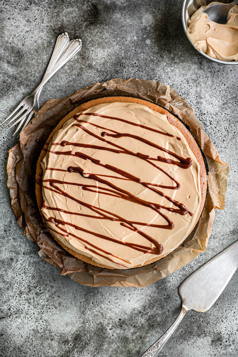 The frosted dulce de leche cheesecake as seen from above with some forks on the side.