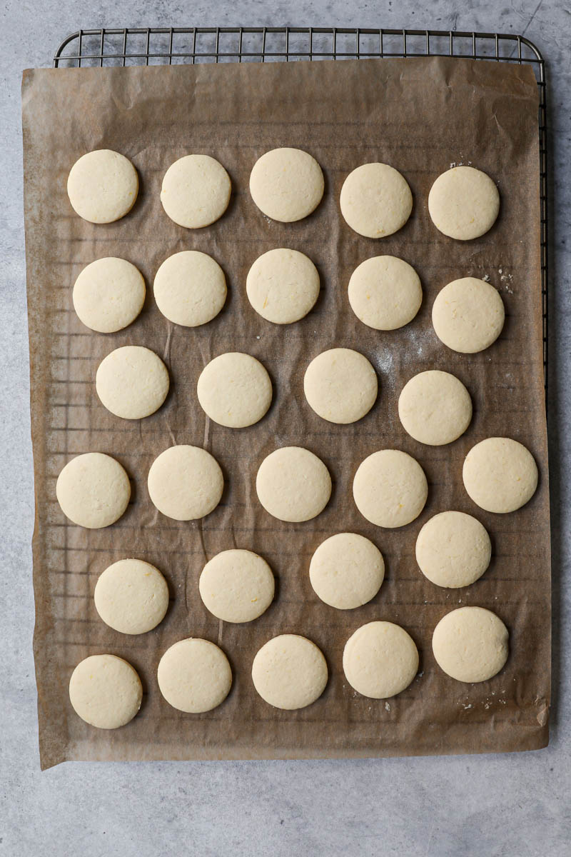 The baked alfajores cookies on top of a wire rack.