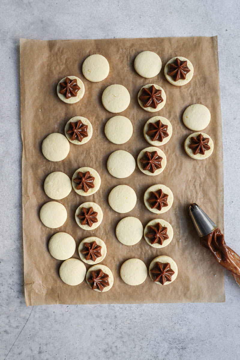 The alfajores cookies on top a piece of parchment paper, turned over and filled with dulce de leche with a piping bag on the side.