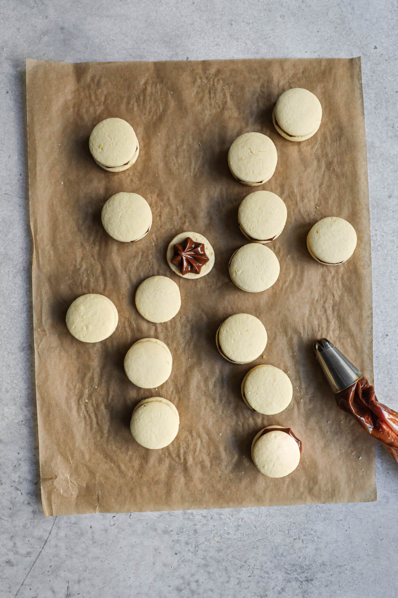 The alfajores cookies on top a piece of parchment paper, turned over, filled with dulce de leche and covered with a second corn-starch cookie, with a piping bag on the side.