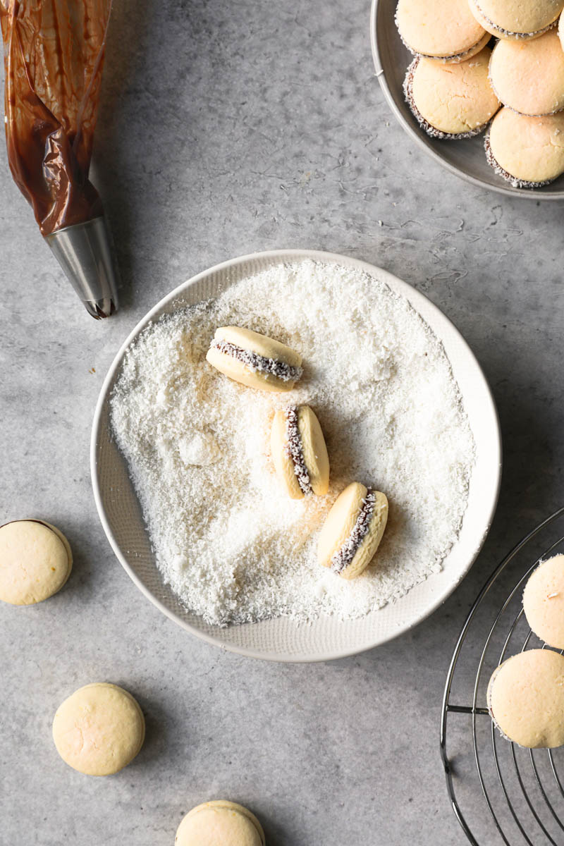 3 alfajores cookies inside a bowl with shredded coconut with some alfajores around the bowl.