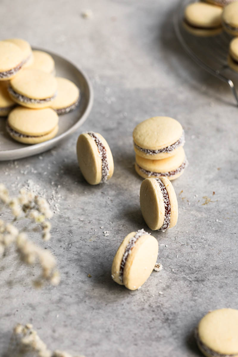 Some alfajores on top of a grey work surface with a plate full of dulce de leche alfajores on the left-hand side of the frame.