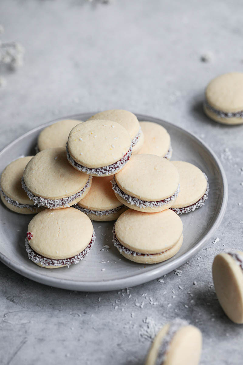 Alfajores stacked on top of a grey plate, and some alfajores on the right side of the frame.