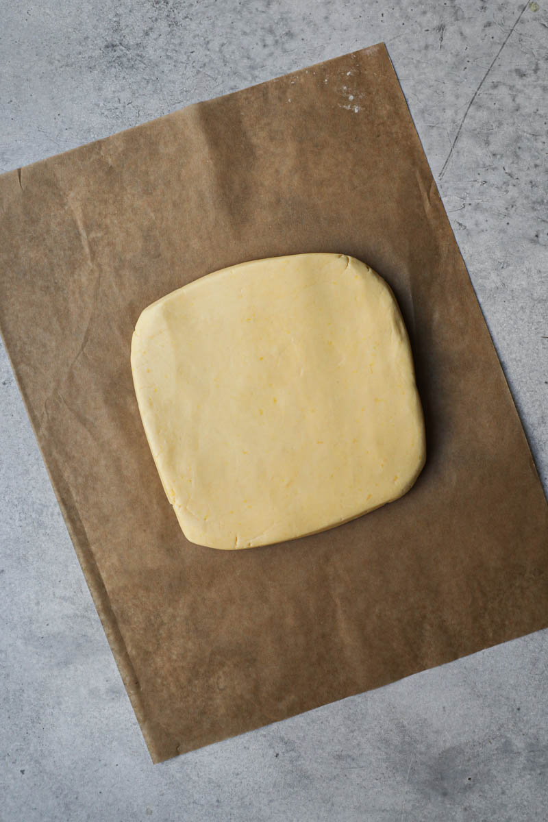 The alfajores cookies dough shaped as a rectangle on top of a piece of brown parchment paper.