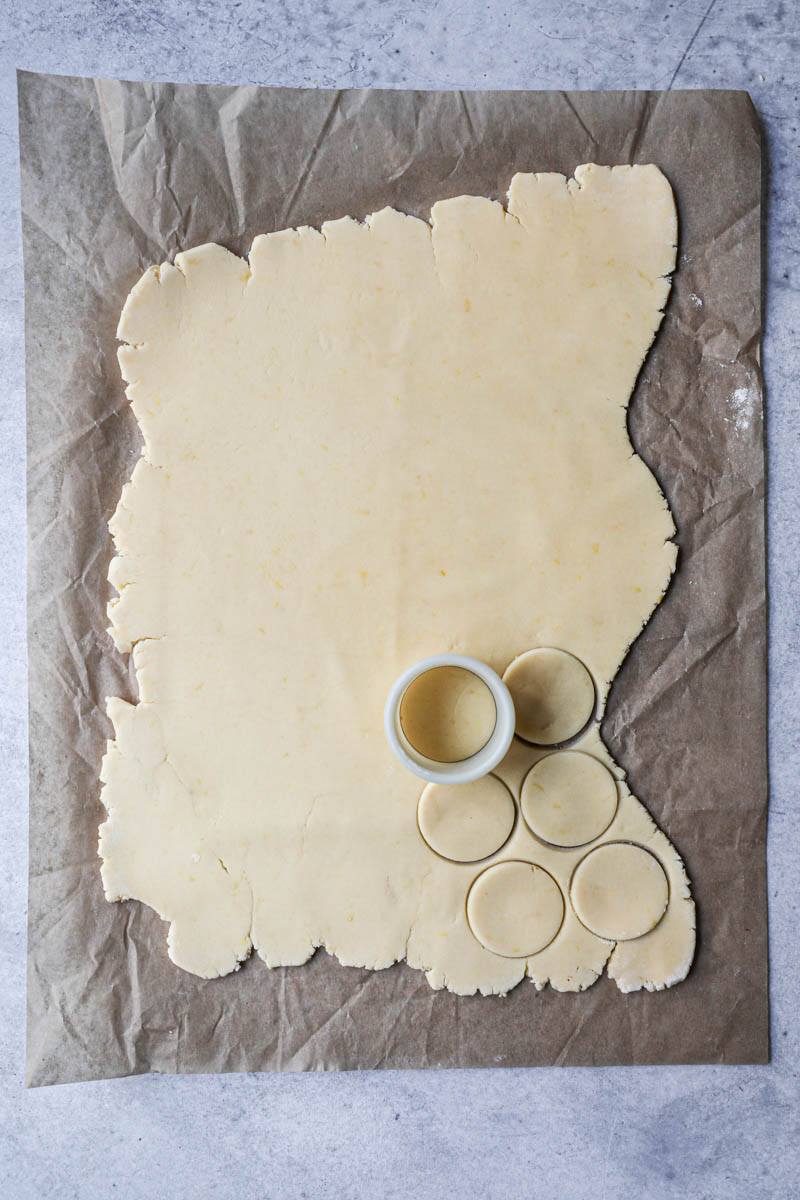 The rolled out cornstarch cookie dough on top of a parchment paper with a cookie cutter on top, and some cookies cut out.