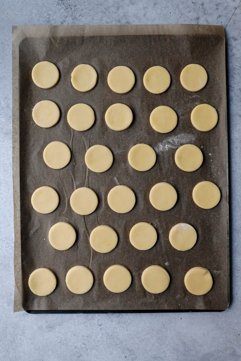 The alfajores cookies on a baking tray lined with parchment paper ready for the oven.