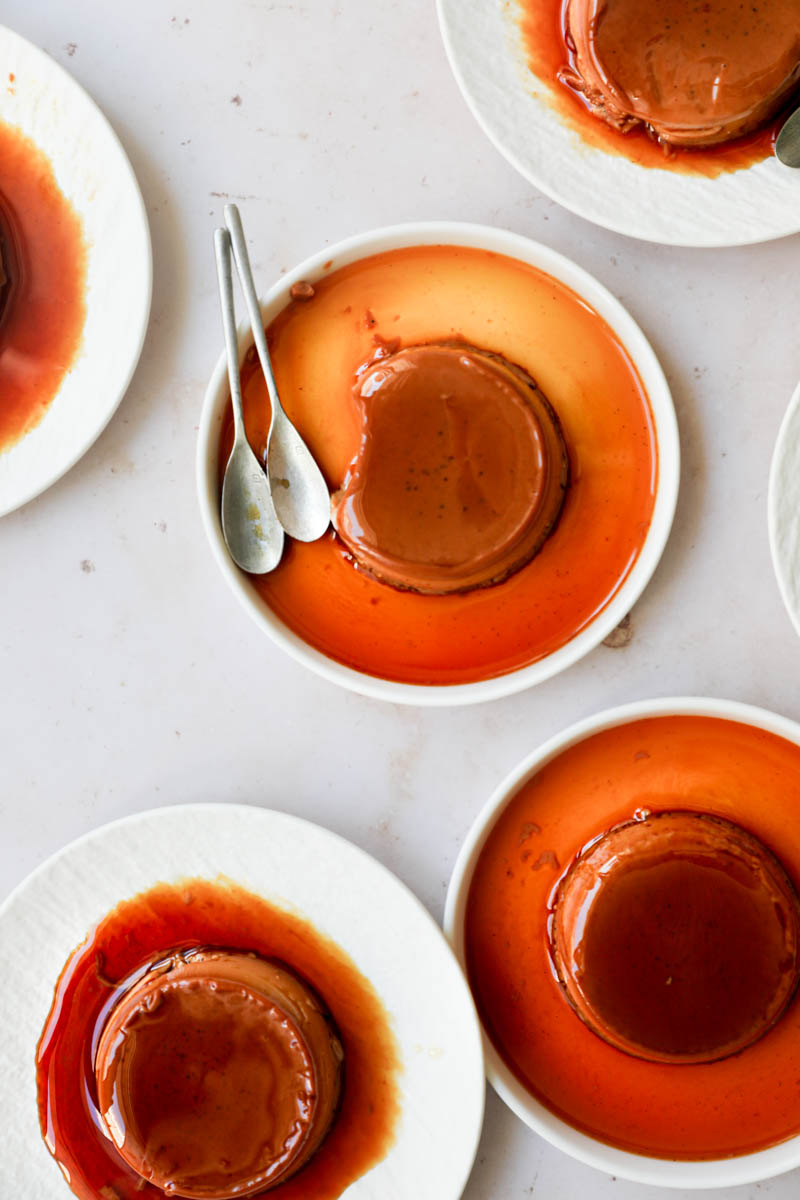 The mini-individual dulce de leche flan on white plates arranged in an irregular manner, as seen from above.
