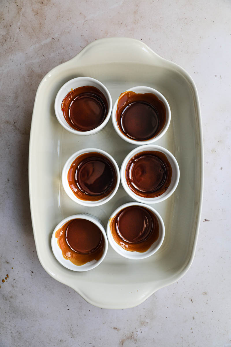 The ramekins lined with caramel for the dulce de leche flan inside a baking tray.