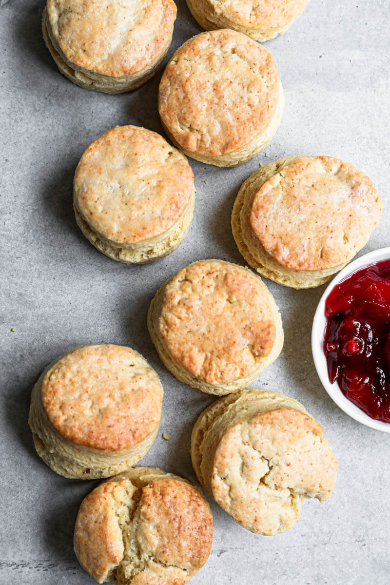 Baked scones disposed in an s shape with a bowl of marmalade on the side