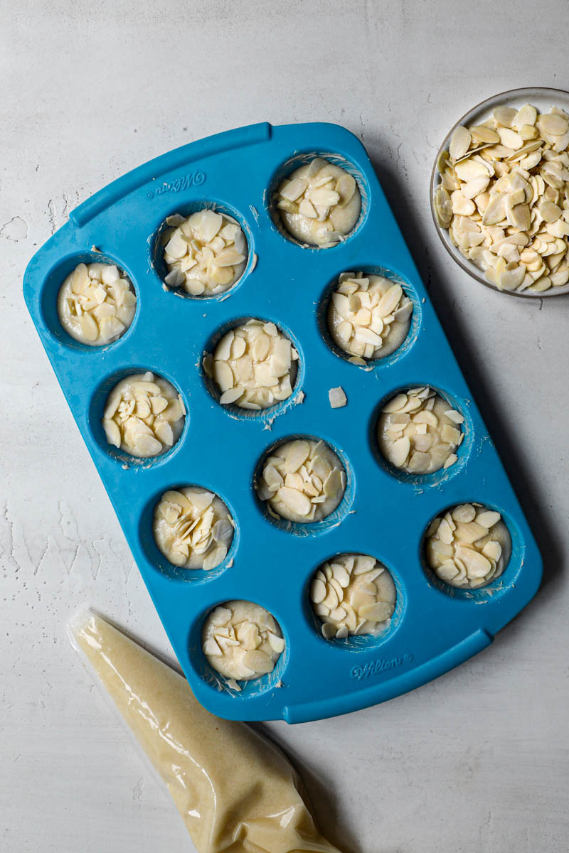 A blue mini muffin pan filled with the French almond cakes with a piping bag on the side and a plate holding sliced almonds on the side.